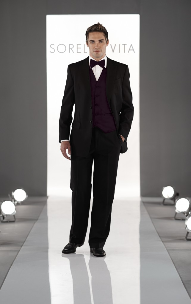 An image of a groomsman wearing a Sorella Vita, black suit with a deep purple bow tie and waist coat.