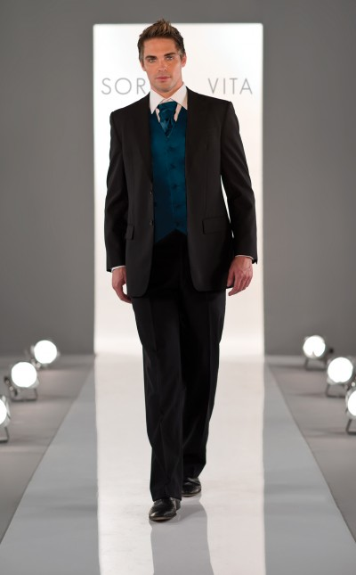 An image of a man wearing a black suit by Sorella Vita, complete with a turquoise cravat and waist coat, sold by Verona Couture in Olney.