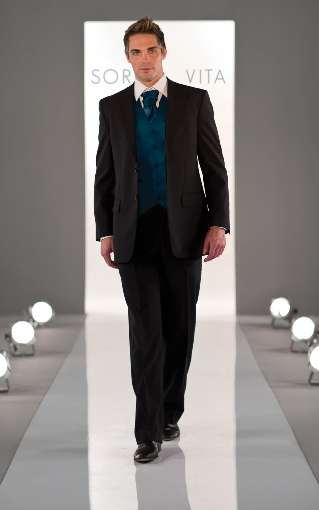 An image showing a man walking down a catwalk wearing a Groomsmen Cravat by Verona Couture in Olney
