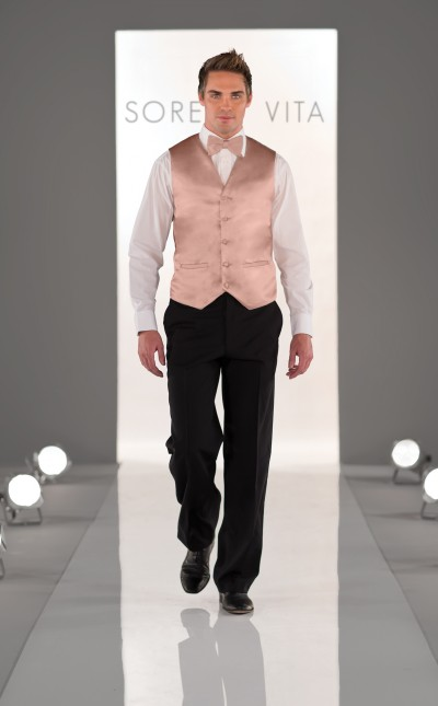 An image of a groomsman wearing a light pink, vest over a white shirt with grey trousers.