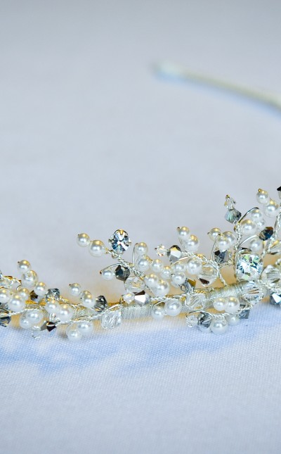 An image of an elegant tiara with silver diamante and peal decoration.