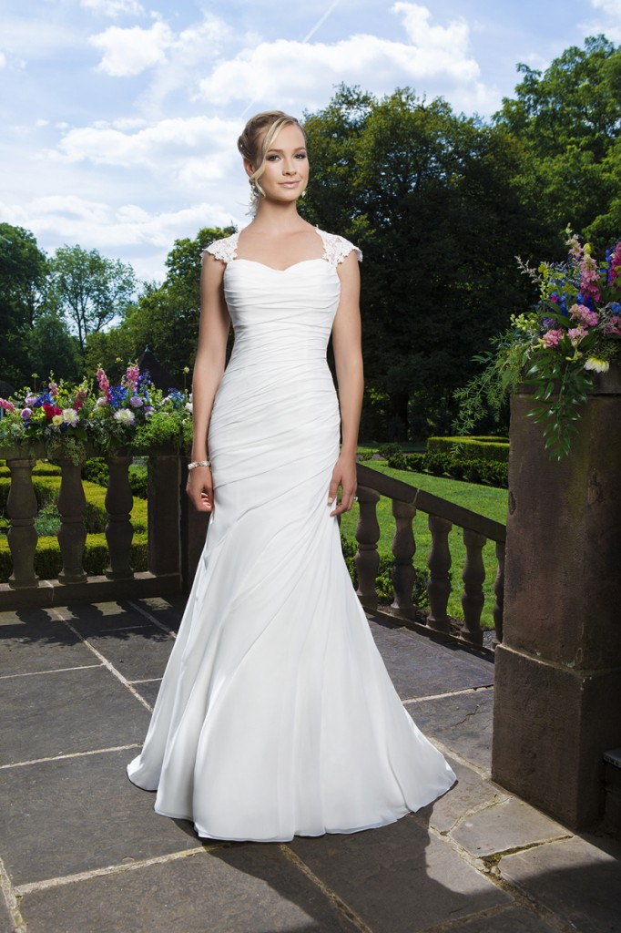 An image of a woman wearing a white Stella York wedding dress with shoulder straps.