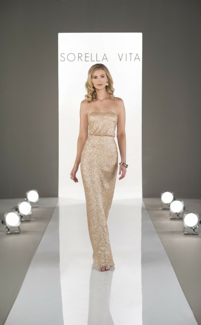 An image of a women walking down a catwalk, wearing a gold occasion dress.