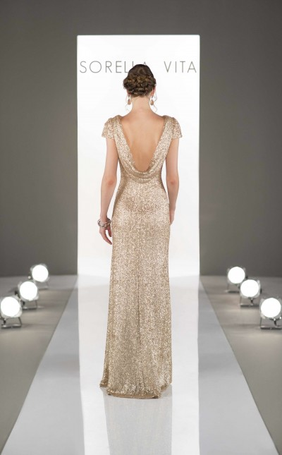 An image showing a woman walking on a catwalk, wearing a metallic Sorella Vita bridesmaid dress from Verona Couture.