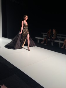 A women walking down the catwalk wearing a black lace evening dress by Verona Couture