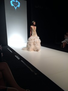 An image showing a women wearing an alternative ruffled wedding dress walking down a catwalk by Verona Couture