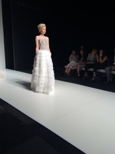 An image showing a women walking down a catwalk wearing a ruffled wedding dress in Northampton