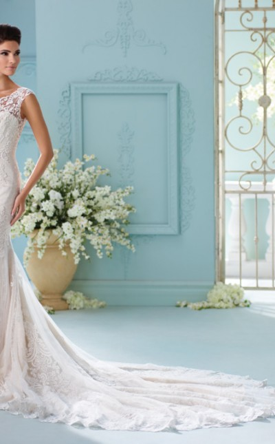 A picture of a woman stood in an elegant Olney setting wearing a David Tutera for Mon Cheri wedding dress in Style 216242
