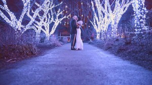 A picture of a couple at their Christmas wedding, surrounded by birch trees wrapped with fairy lights