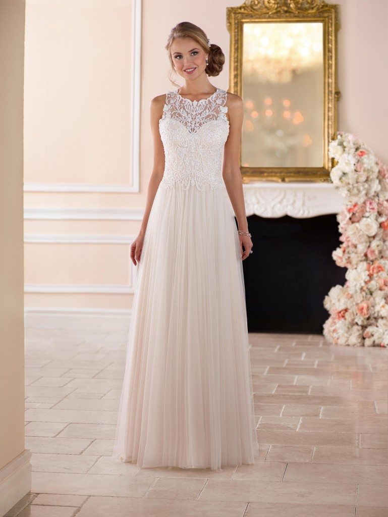 An image showing a classic Stella York floor length pleated wedding dress inside with a fireplace in the background.