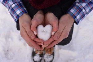 An image showing male and female hands holding snow moulded in to a love heart shape with a ring inside.