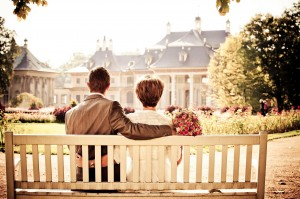An image showing a happy couple sitting on a wooden benech looking at their wedding locations