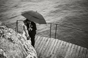 An image of a couple standing in the rain, underneath an umbrella on their wedding day.