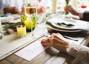 An image of a bride sat at a wedding table with wedding favours on it.