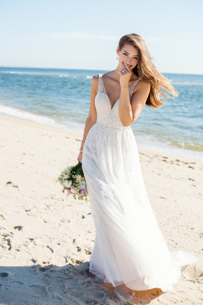 An image of a woman wearing a light and floaty Mon Cheri wedding dress on the beach.