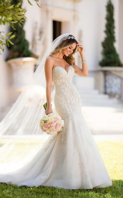 An image of a woman wearing a fitted, strapless wedding dress with a sweetheart neckline, designed by Stella York with the style code 6654.