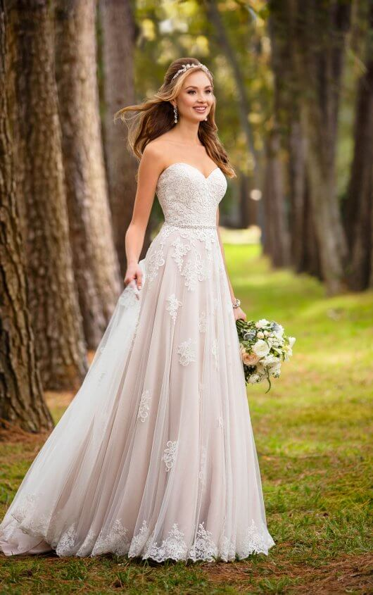 An image of a woman standing outside in a nude and white Stella York wedding dress in style number 6466.