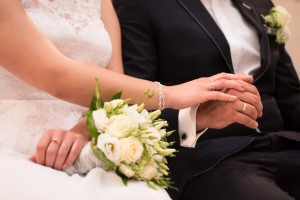 An image of bride and groom holding each others hands. Both the bride and groom are wearing wedding rings and the the bride is holding a bouquet.