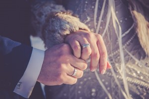 An image of the hands of a bride and groom that are getting married in the winter. The bride is wearing a fur coat.