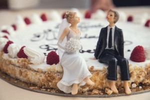 A close up image of two figurines sat on a untraditional wedding cake.
