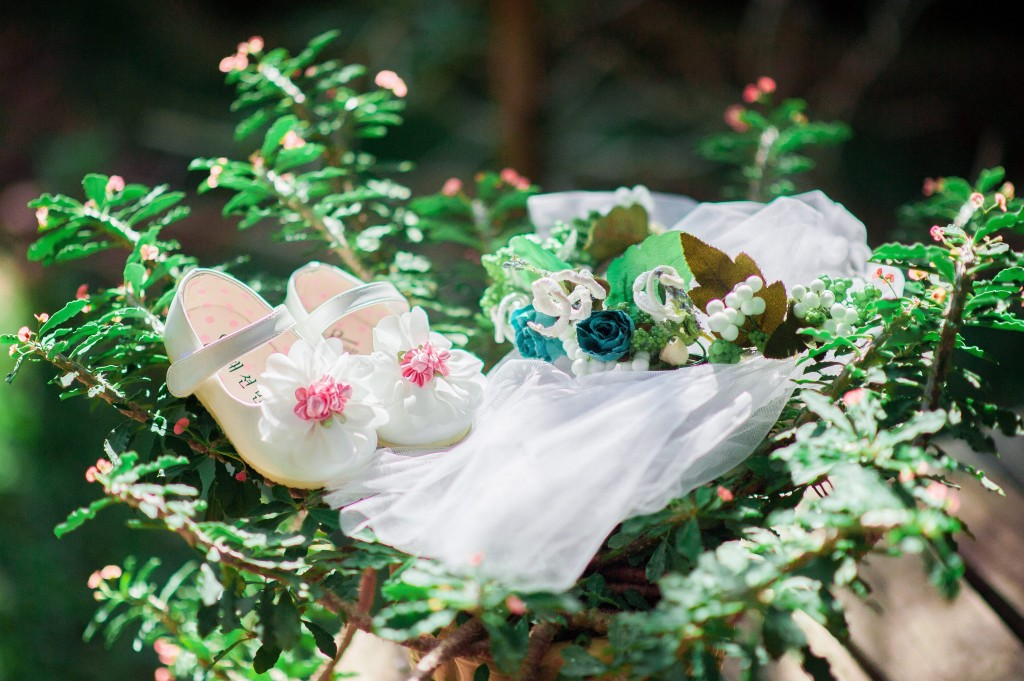 An image of children's wedding shoes and a veil.