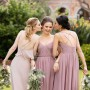 An image of three women standing together at a wedding reception, wearing Sorella Vita bridesmaid dresses.