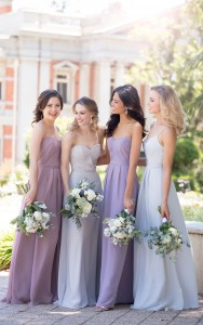 An image of four girls in pastel coloured bridesmaid dresses standing next to each other and smiling for a photograph.