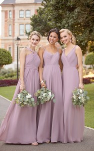 An image of three women carrying small bouquets of flowers, wearing dusty pink wedding dresses outside of a stately home.
