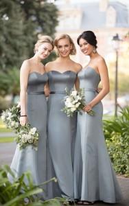 An image of three women wearing dusty green Sorella Vita bridesmaid dresses with a sweetheart neckline.